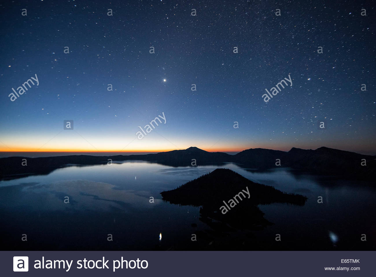 Thousands of stars and the planet Venus shine over Crater Lake in Oregon just before sunrise. Stock Photo