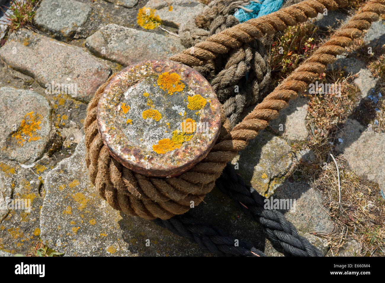 A rusty mooring post with hemp rope from a ship looped around it - Stock Image