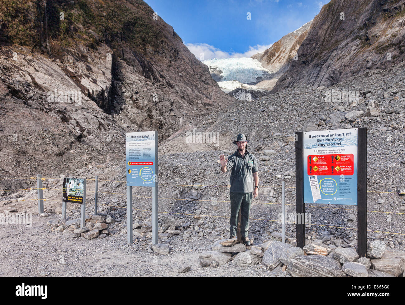 Franz Josef Glacier, with sign warning of how dangerous it is. Ranger is a cardboard cutout. - Stock Image