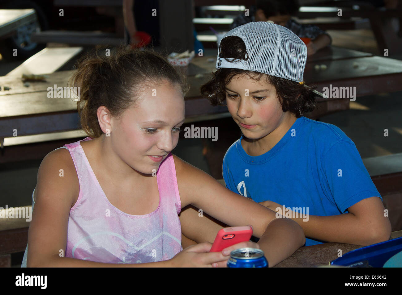 A boy and girl texting and having fun with a cellphone. - Stock Image