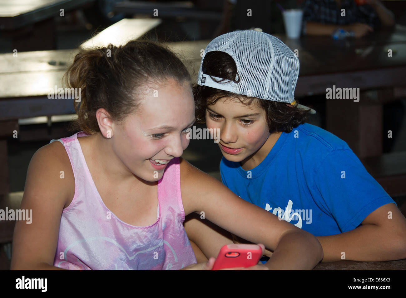 A boy and girl laughing as they are texting and having fun with a cellphone. - Stock Image