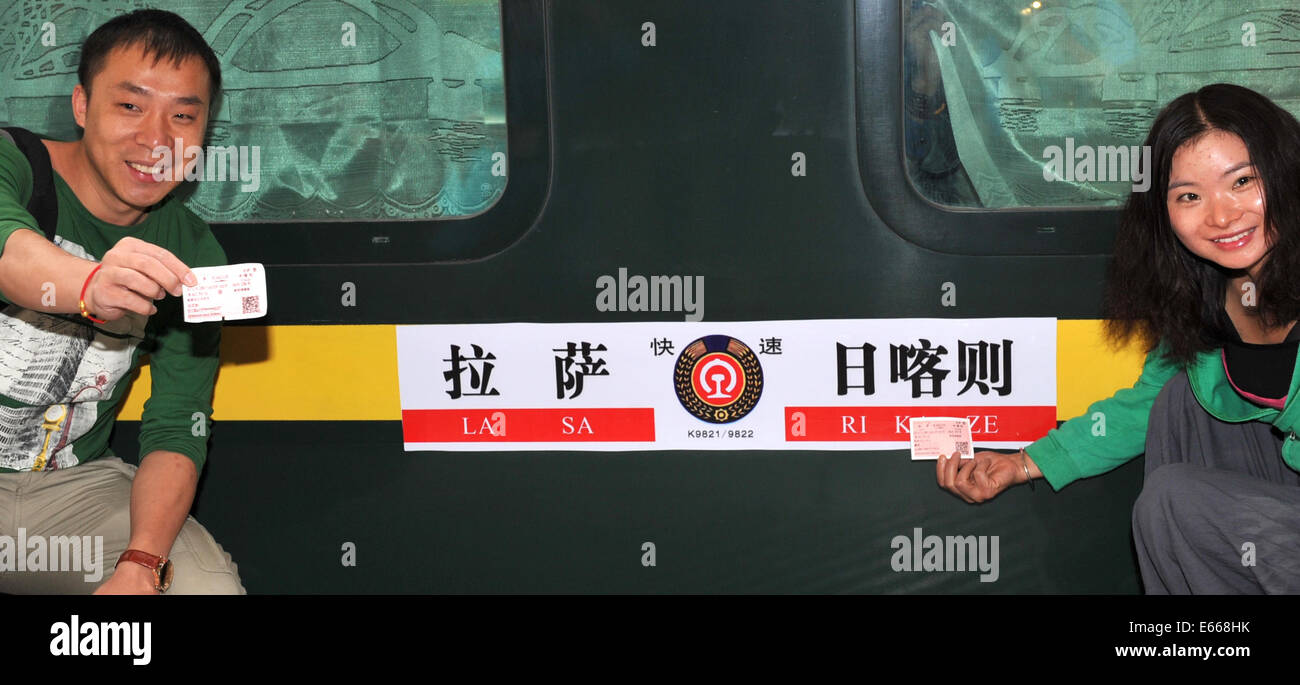 Lhasa, China's Tibet Autonomous Region. 16th Aug, 2014. Passengers to take the train from Lhasa to Xigaze poses - Stock Image