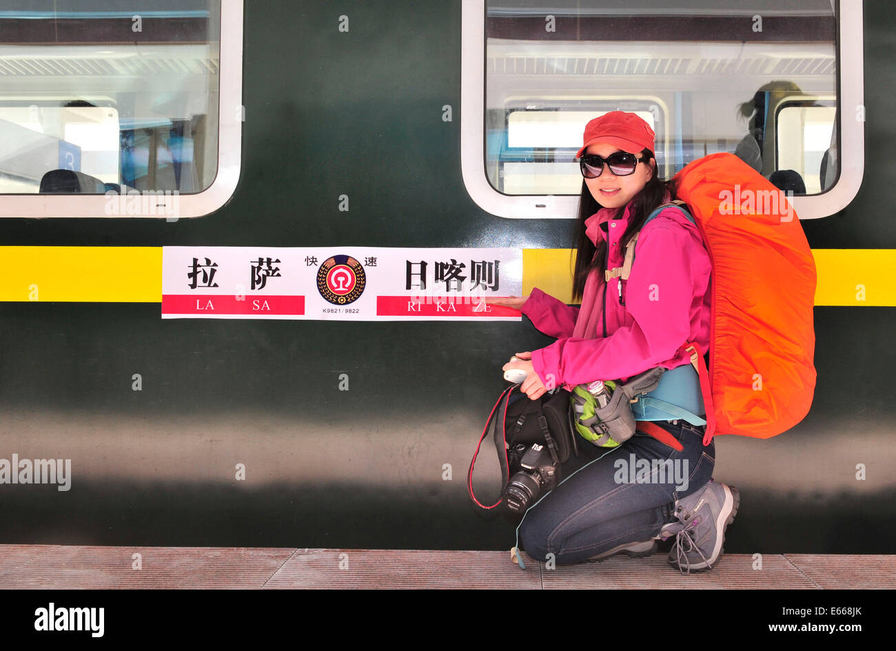 Xigaze, China's Tibet Autonomous Region. 16th Aug, 2014. A passenger poses for photo with the train from Lhasa - Stock Image