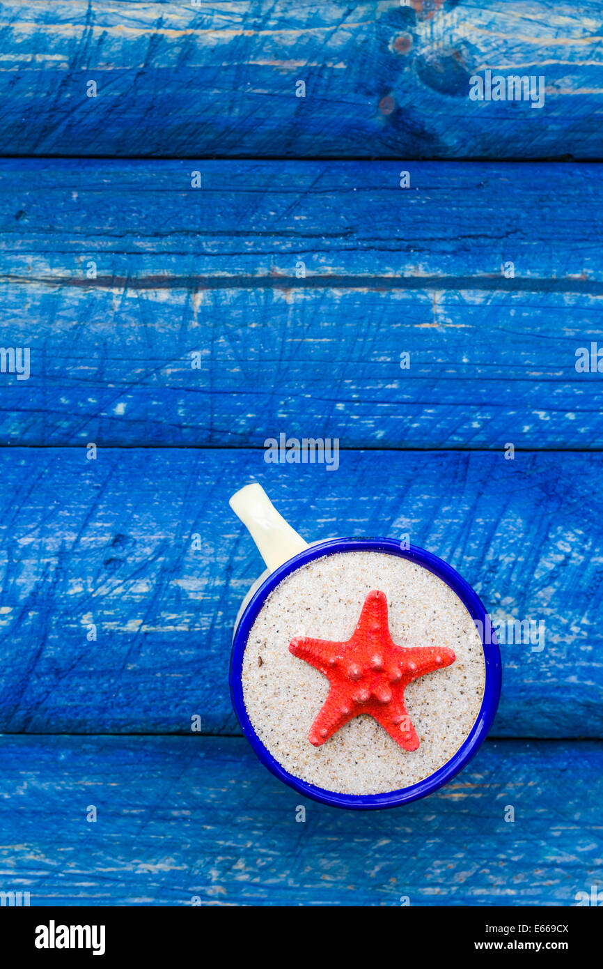 Scallop color in the cup on blue table - Stock Image