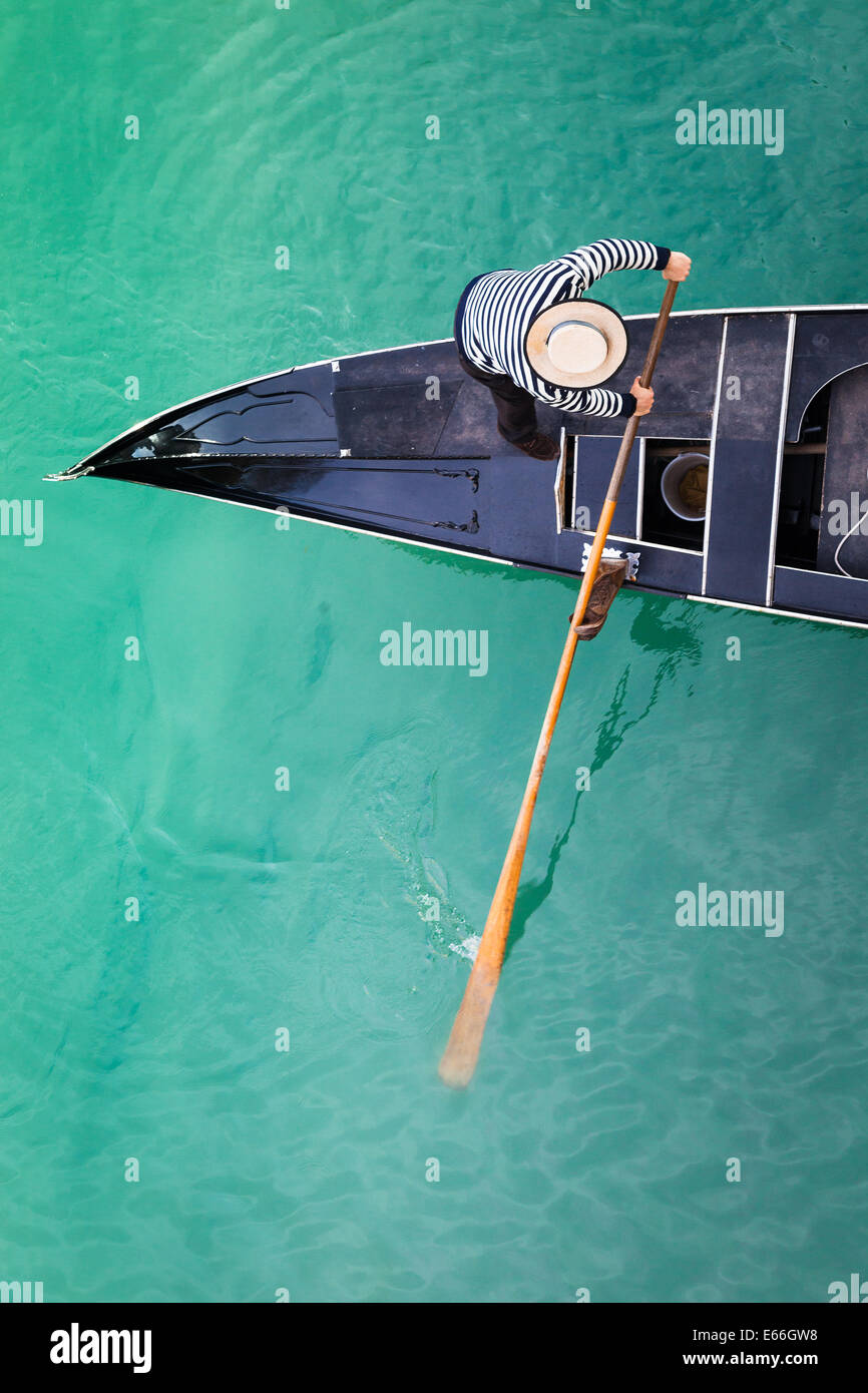 View of gondola and gondolier from above with a bridge across the Grand canal - Stock Image