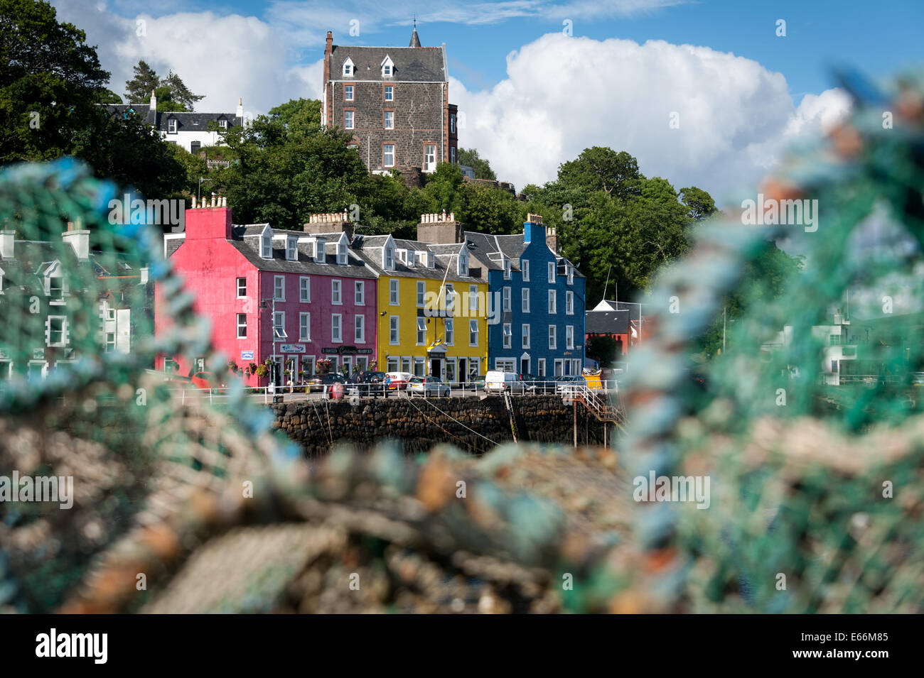 Colourful buildings on the waterfront at Tobermory, Isle of Mull, Scotland seen framed by lobster pots. Stock Photo
