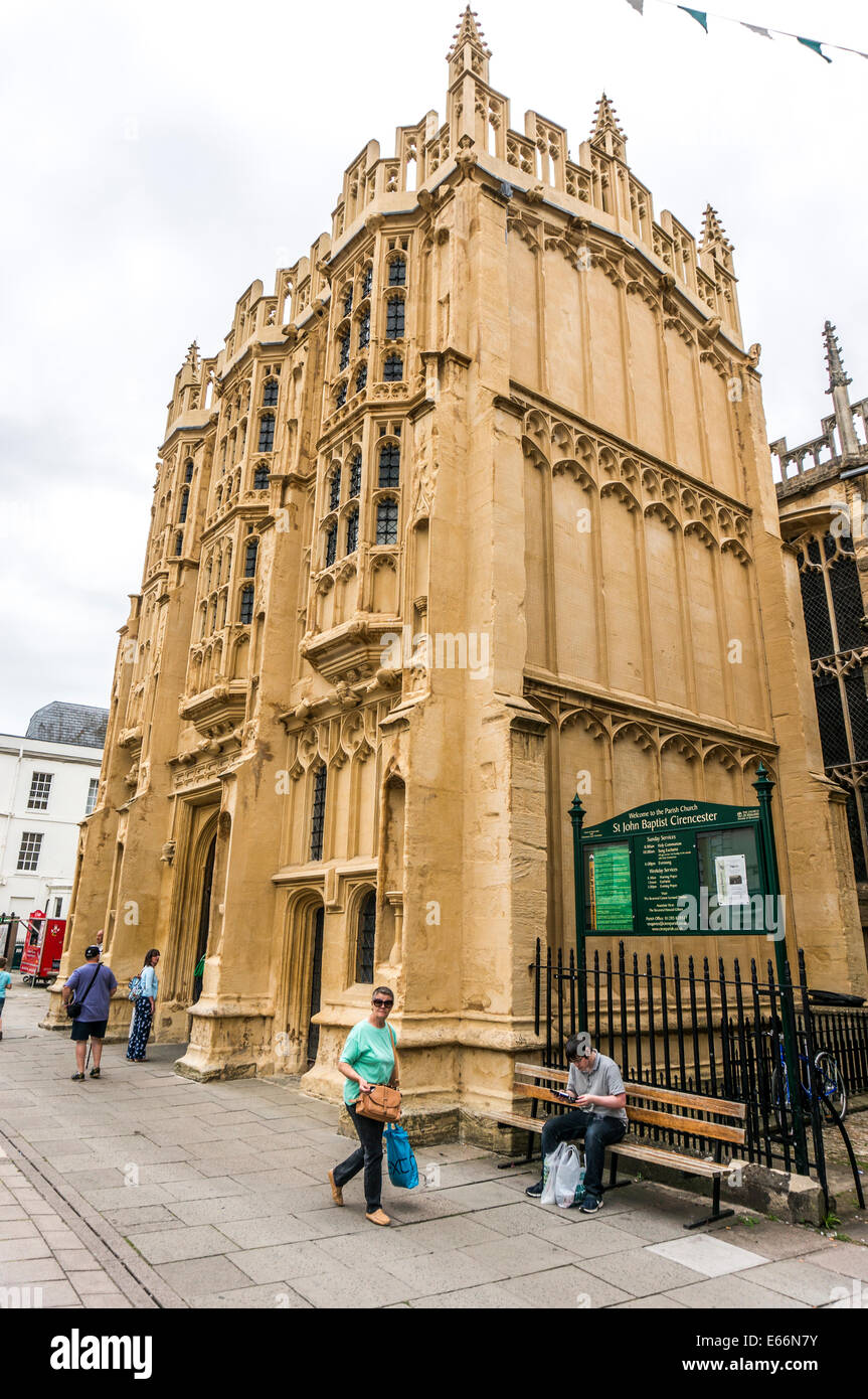 The 15th century south porch of the historic Church of St John Baptist, with passers by, Cirencester centre, Cotswolds, - Stock Image