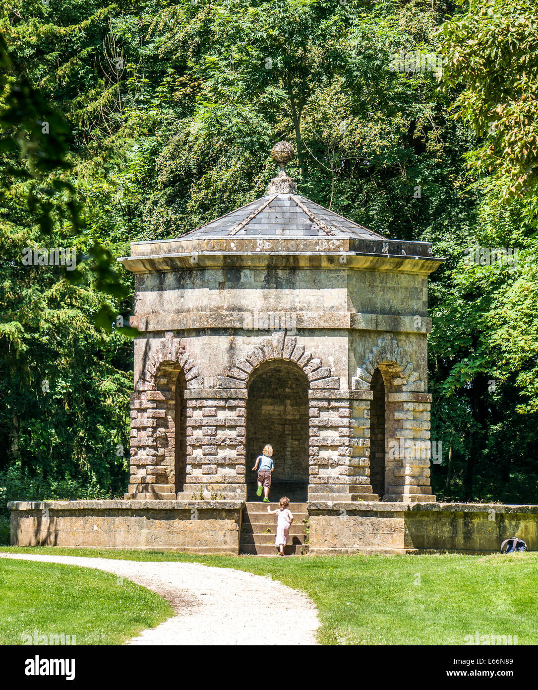Two curious young children climbing the steps to The Hexagon folly, on the Bathurst Estate, Cirencester Park, Cotswolds, - Stock Image