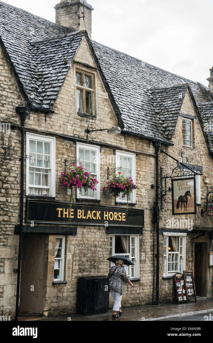 Woman walking past The Black Horse public house in the rain, town centre, Cirencester, Cotswolds, Gloucestershire, - Stock Image
