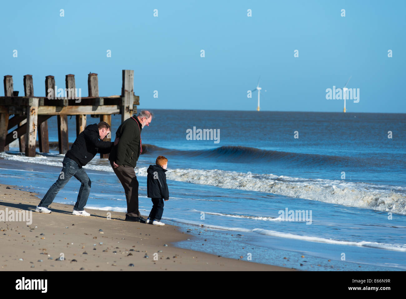 Three generations of men on Great Yarmouth beach. - Stock Image