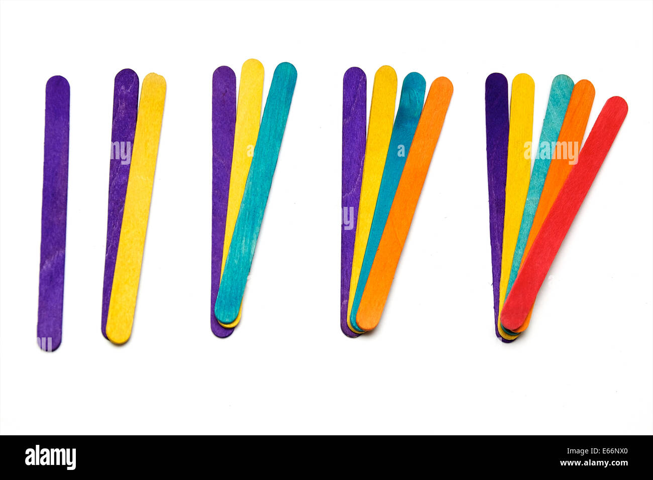 Various colored popsicle craft sticks are in groups each color adds another number over white. - Stock Image