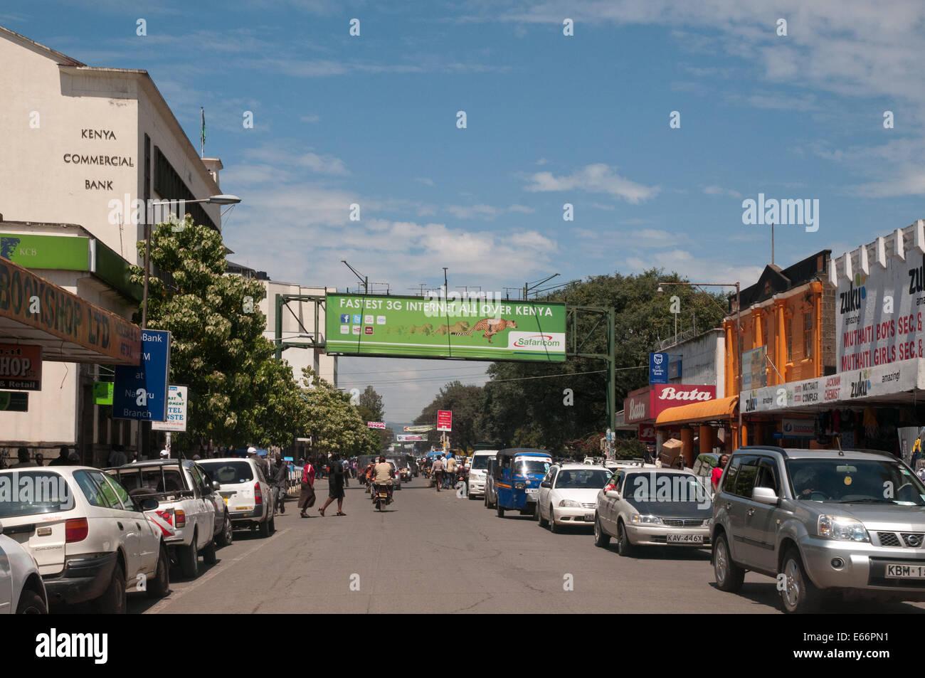 People and traffic on Kenyatta Avenue Nakuru Kenya East Africa with advertising hoarding for 3g Network Stock Photo