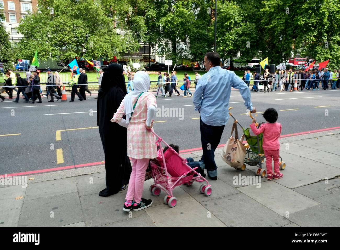 Muslim families look on as the anti ISIS demo approaches Marble arch - Stock Image
