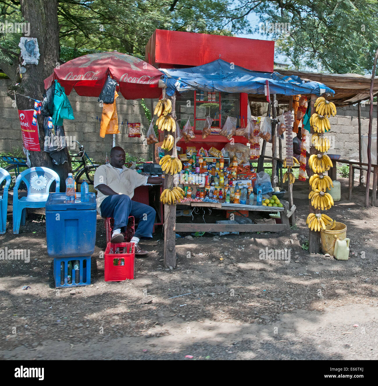 Man dozing at side of his market stall offering bananas soft drinks sweets and snacks on outskirts of Nakuru town - Stock Image