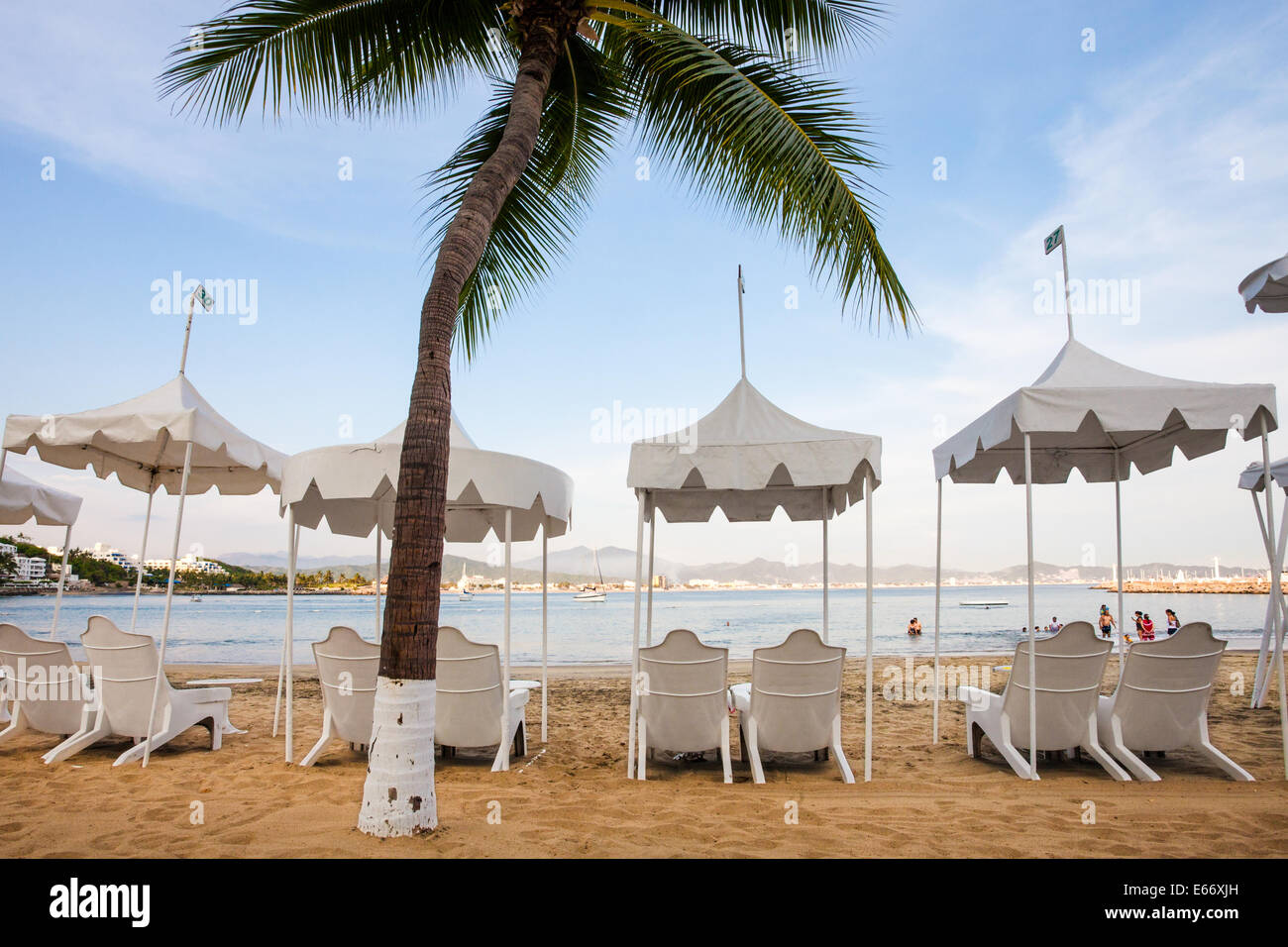 Beach chairs and palm at the Las Hadas Resort in Manzanillo, Colima. - Stock Image