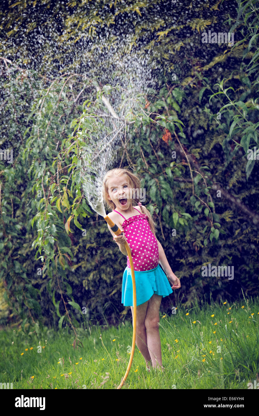 Young girl playing with water and hosepipe in the garden. - Stock Image