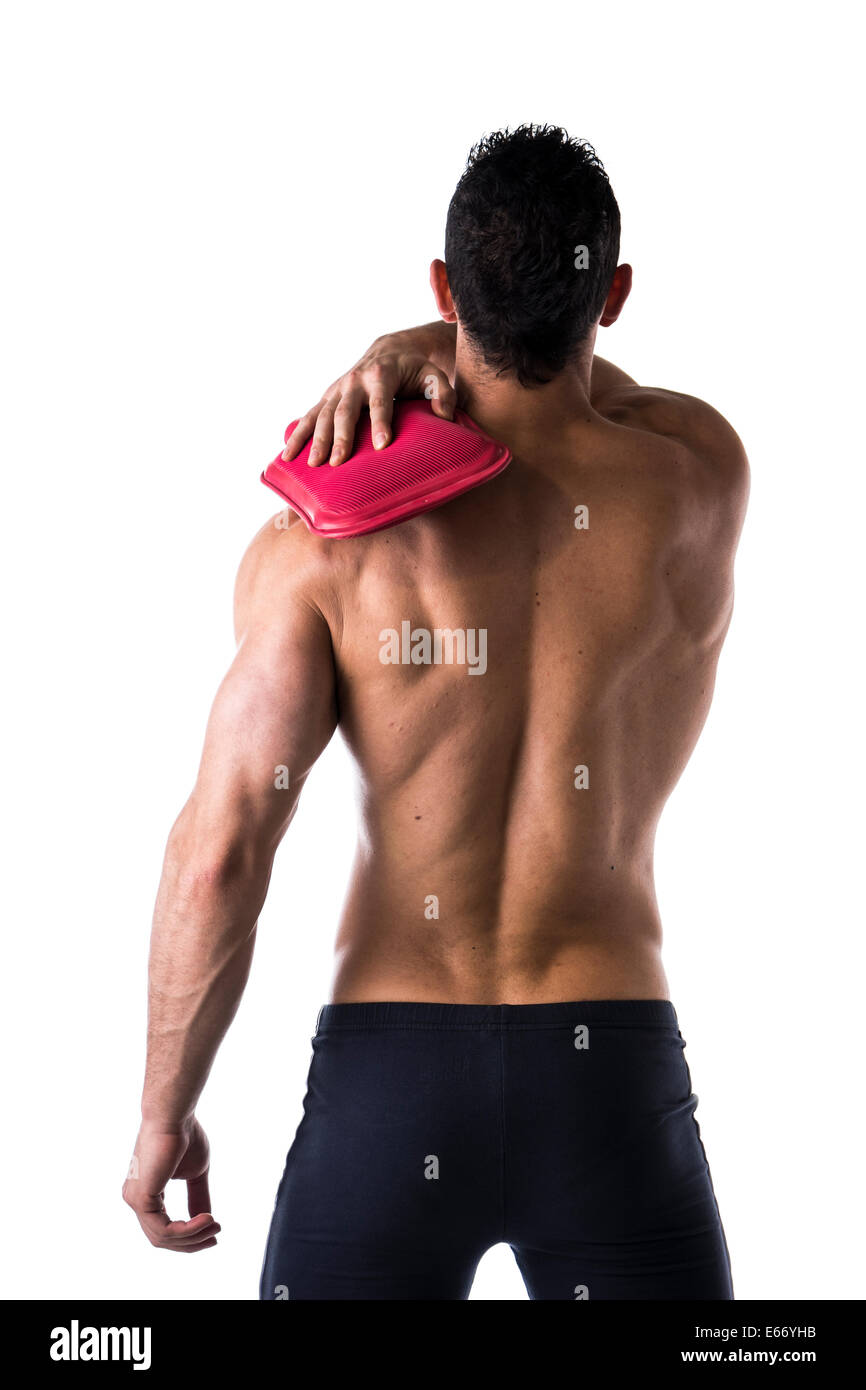 Back of muscular young man with shoulder pain, holding hot water bottle, isolated on white - Stock Image
