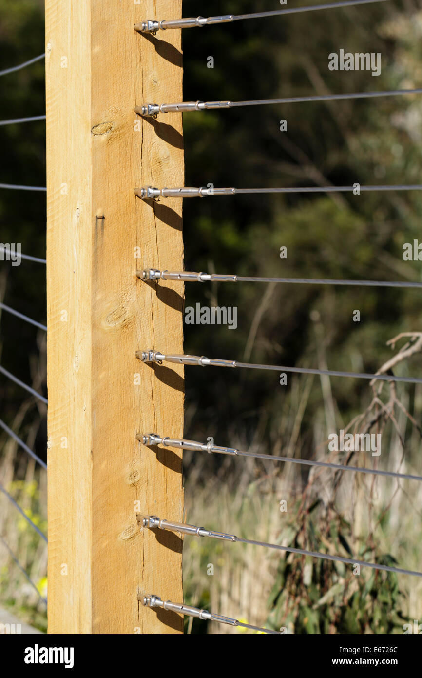 Wooden fence post with tightly tensioned fence wire - Stock Image