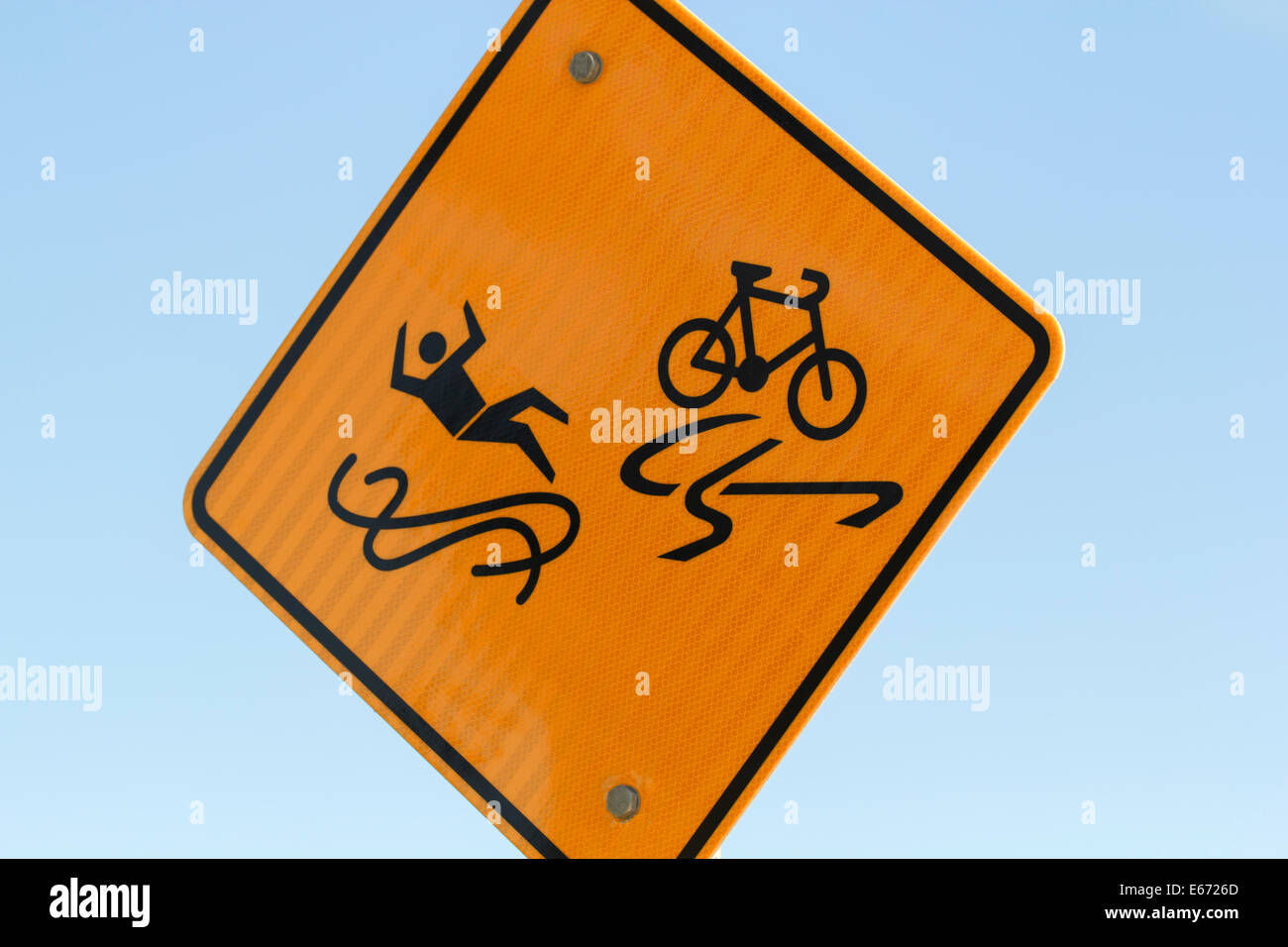 Slippery when wet sign illustrating human and bike on slippery road surface Stock Photo