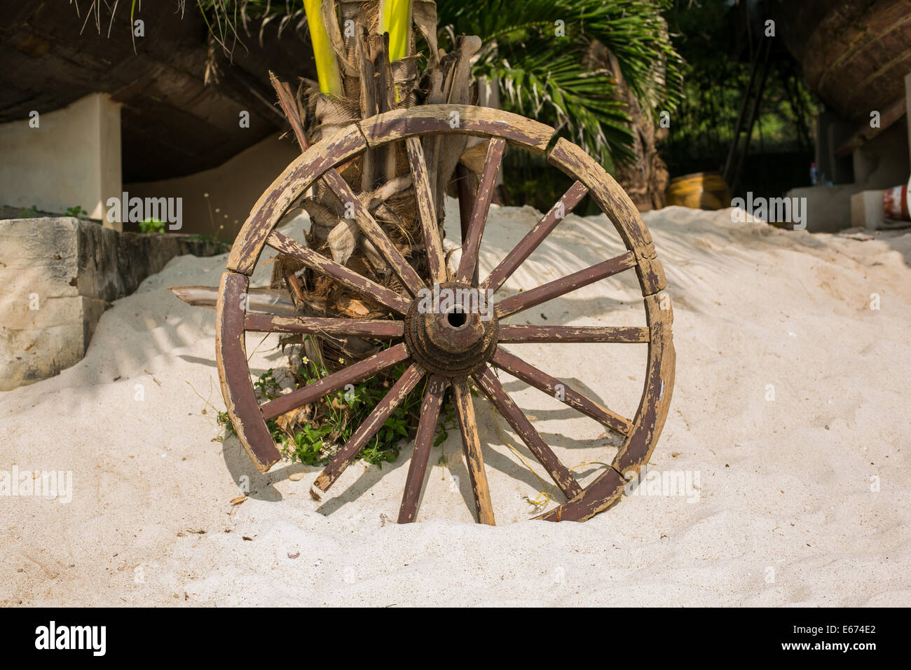 Old brown wooden wheel on sand beach. Stock Photo