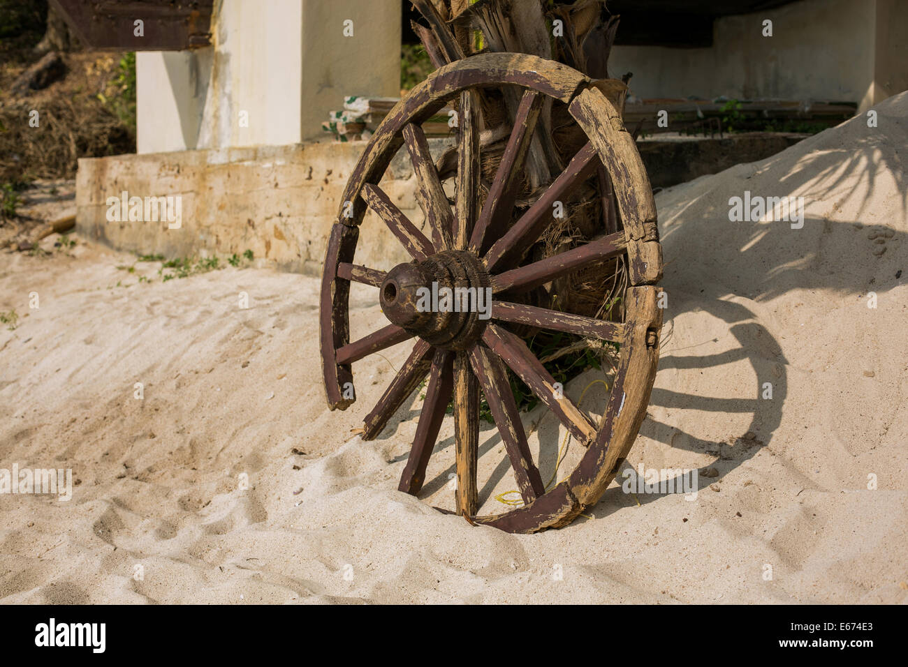 Old brown wooden wheel on sand beach.Stock Photo