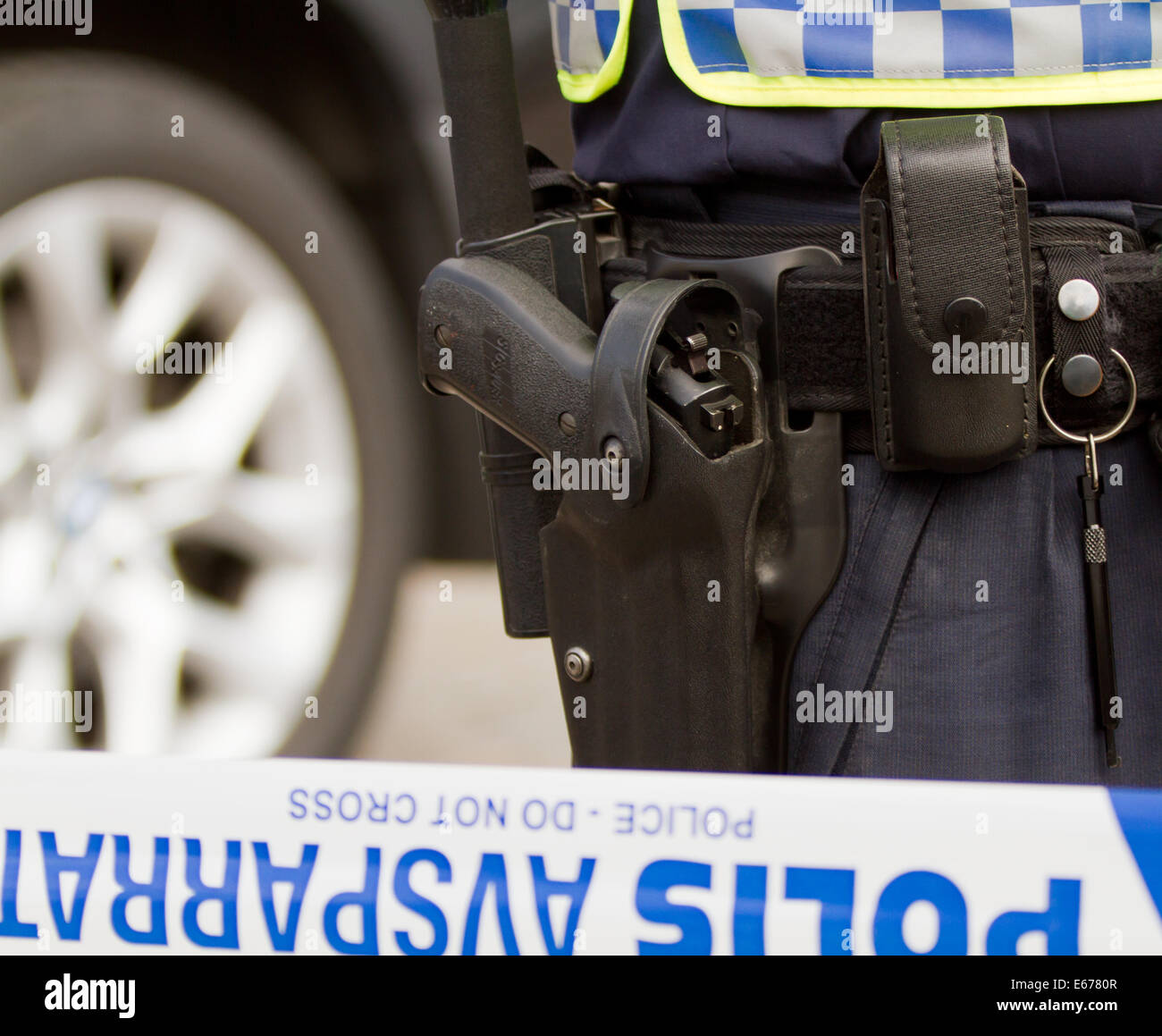 Gun in a gun belt of a Swedish policeman while standing behind the line that has sealed off public entrance. Stock Photo