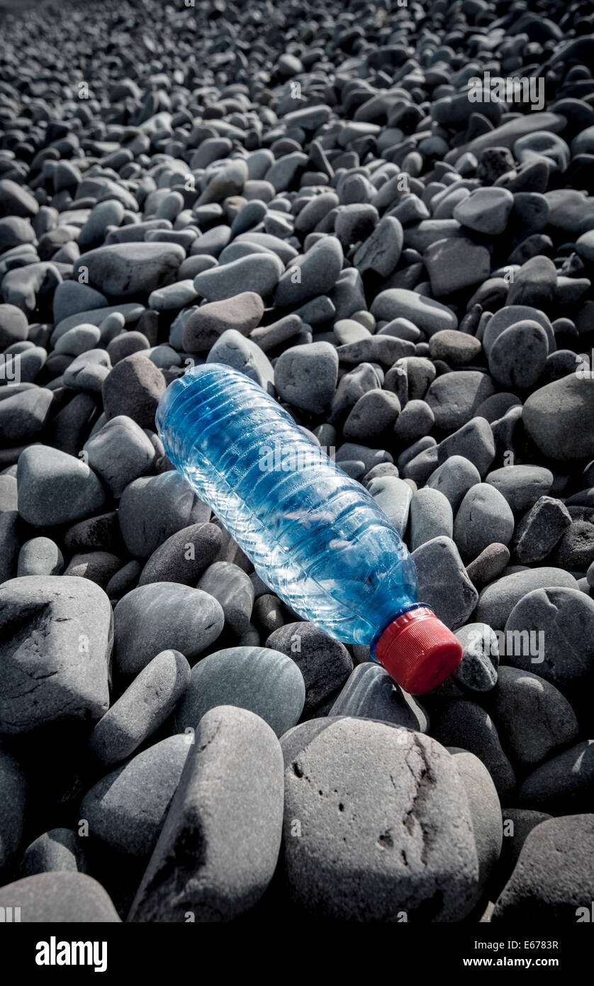 A plastic bottle discarded on a pebble beach - Stock Image