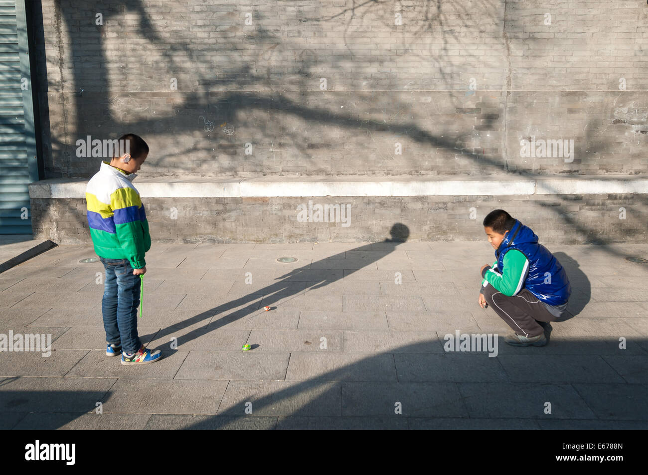 Two young boys playing outdoors in a Beijing hutong - Stock Image
