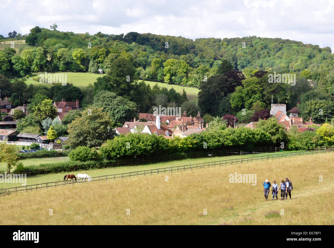 Bucks - Chiltern Hills - Turville - meadow foreground -  walkers - cottage rooftops - church tower - wooded hills - Stock Image