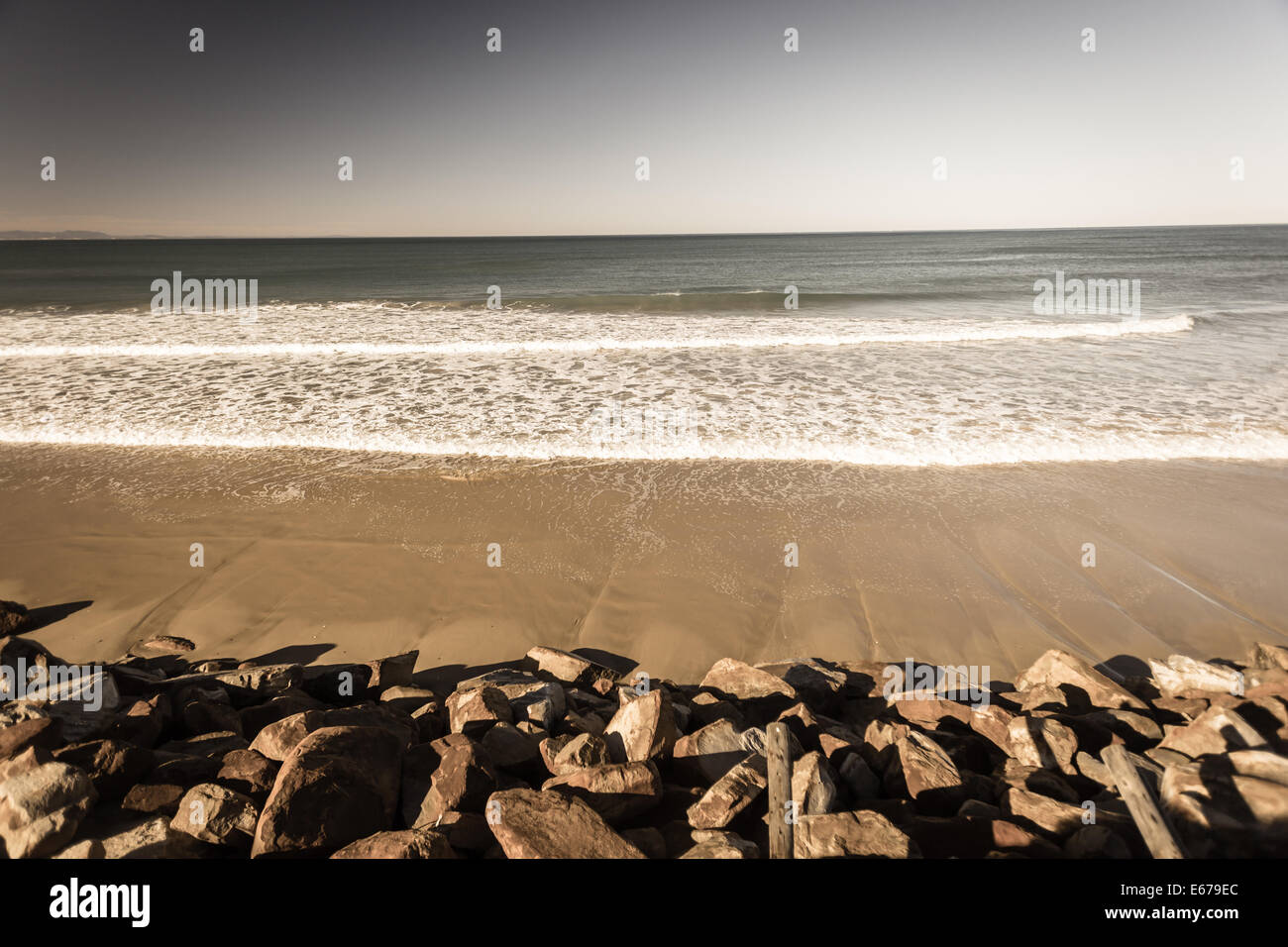 Beach sands into ocean water waves with distant ocean horizon in sepia vintage landscape contrast - Stock Image