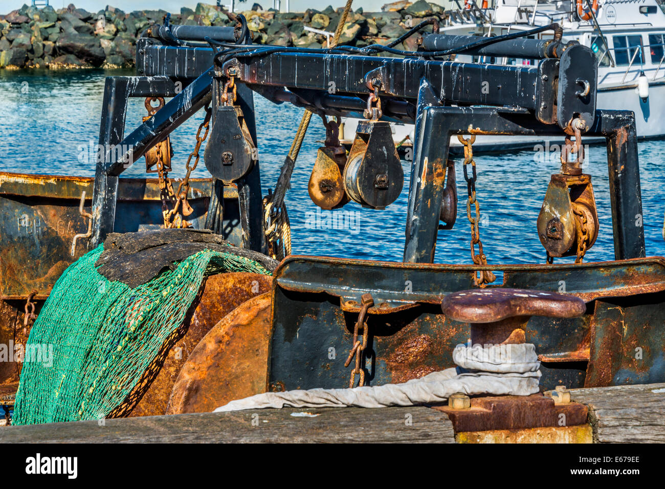 Fishing boat with heavy fishing equipment, rusted and weathered chains ropes pulleys and fishing nets moored Eden - Stock Image