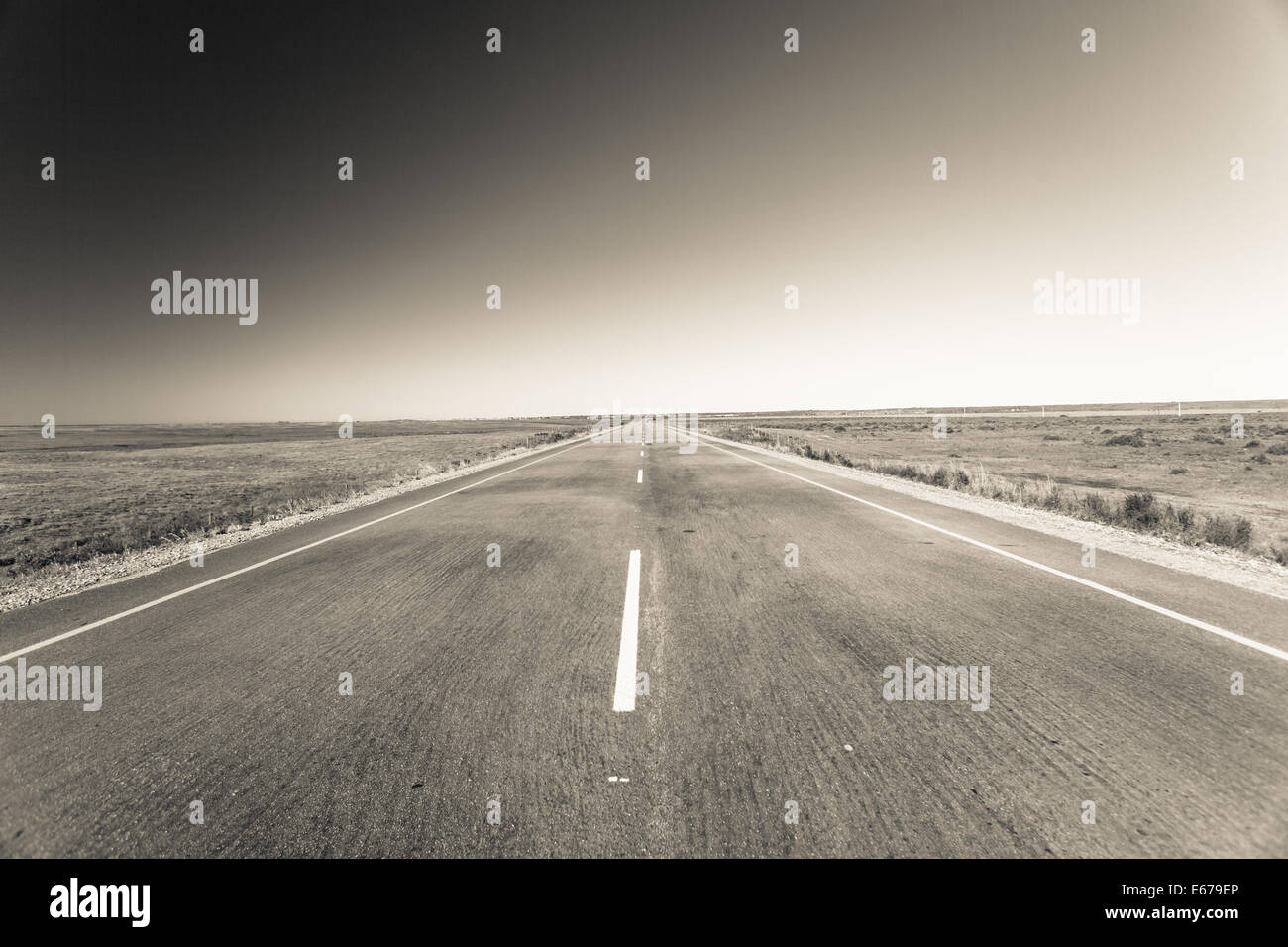 Road route long straight into horizon distance in vintage black white tones - Stock Image