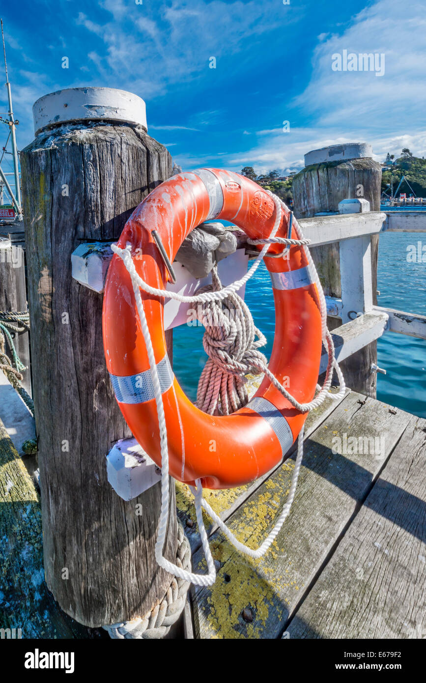 Bright orange life buoy and ropes on old weathered post, Eden Harbour, Eden, South Coast NSW, Australia - Stock Image