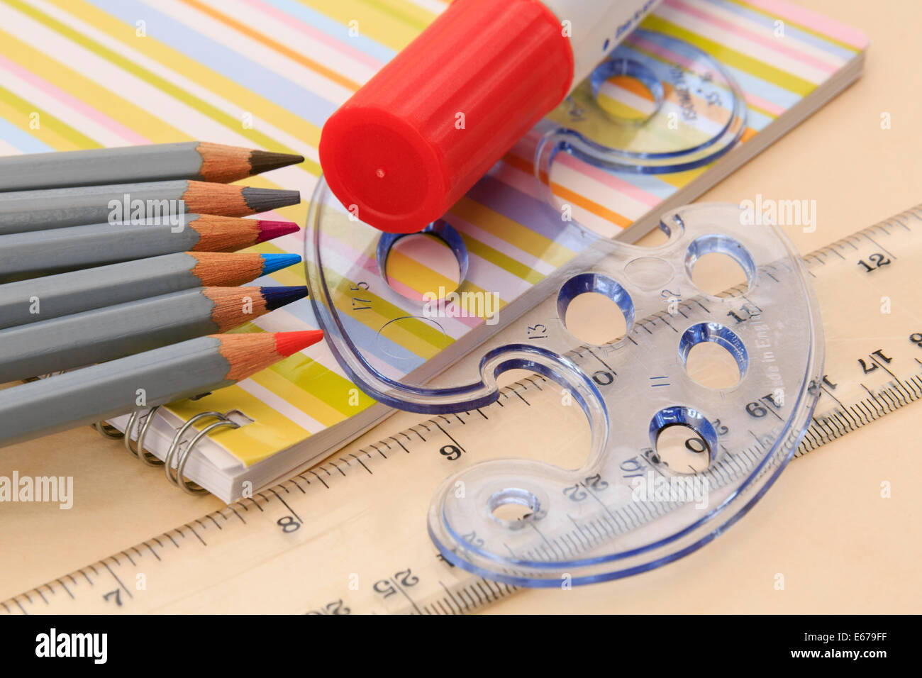 Educational drawing equipment notebook, coloured pencils, glue stick, ruler and geometric shapes stencil on a desktop - Stock Image