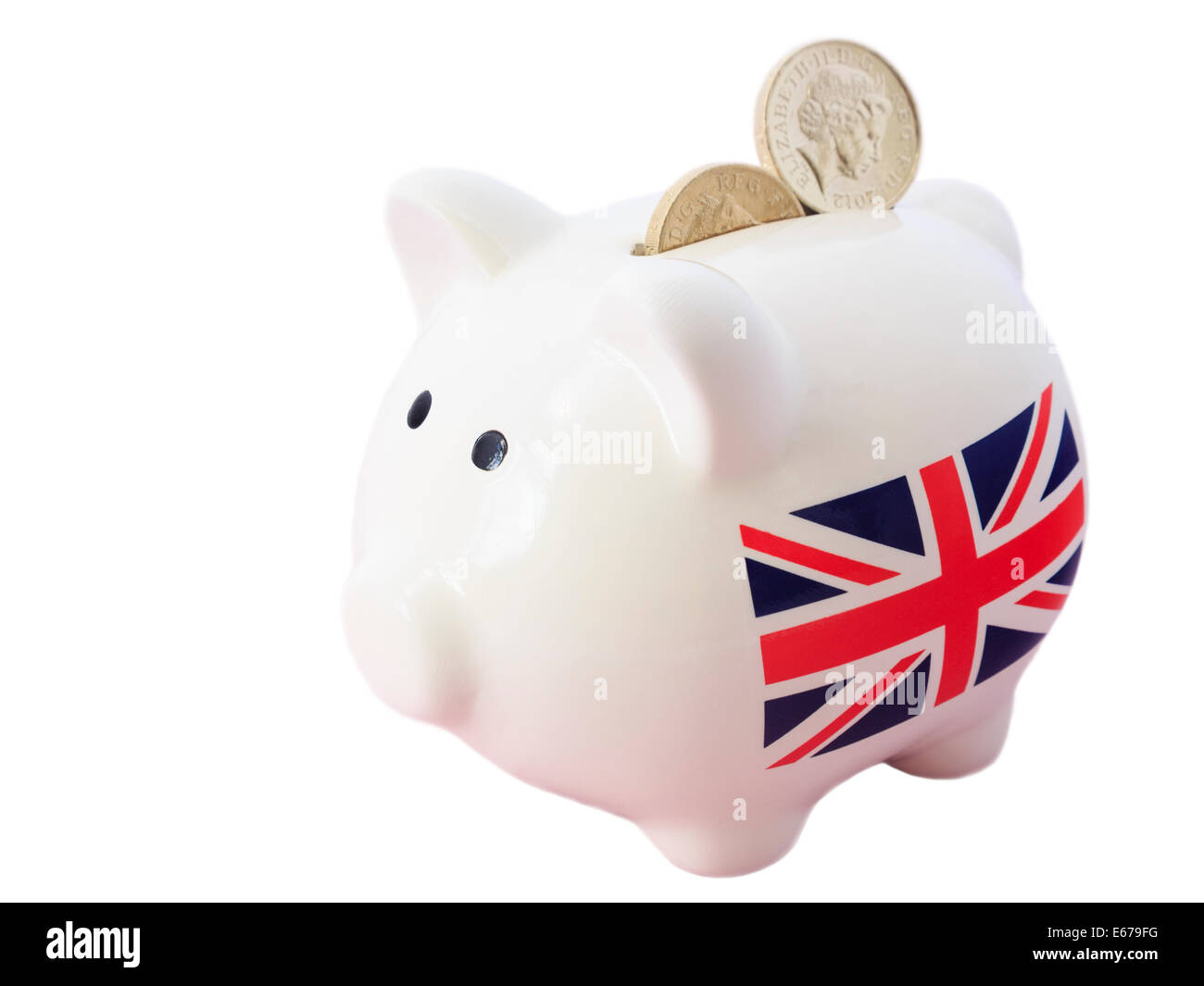 Piggy bank with British Union Jack and sterling pound coins in slot to illustrate saving money financial growth - Stock Image
