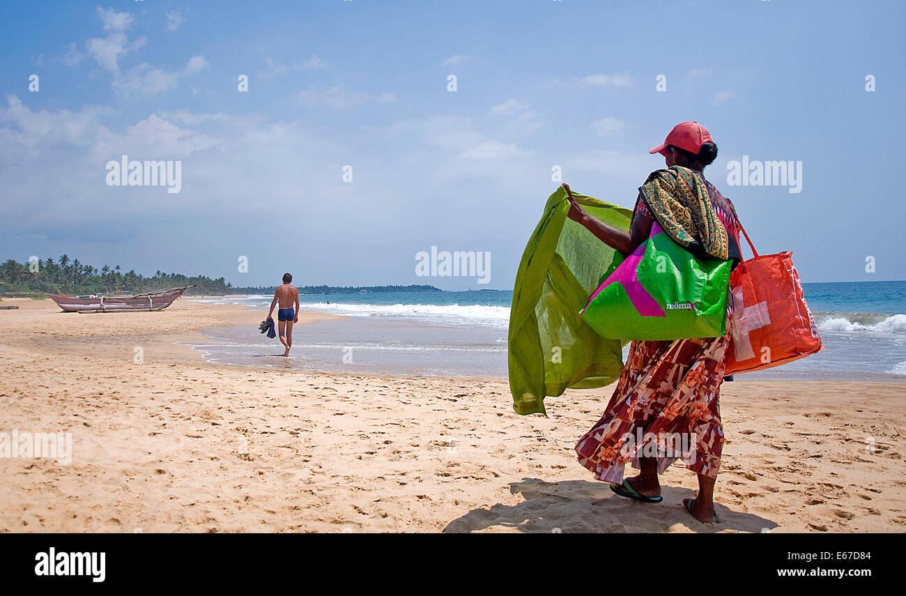 A beach vendor sells sarong to  tourist in Sri Lanka - Stock Image
