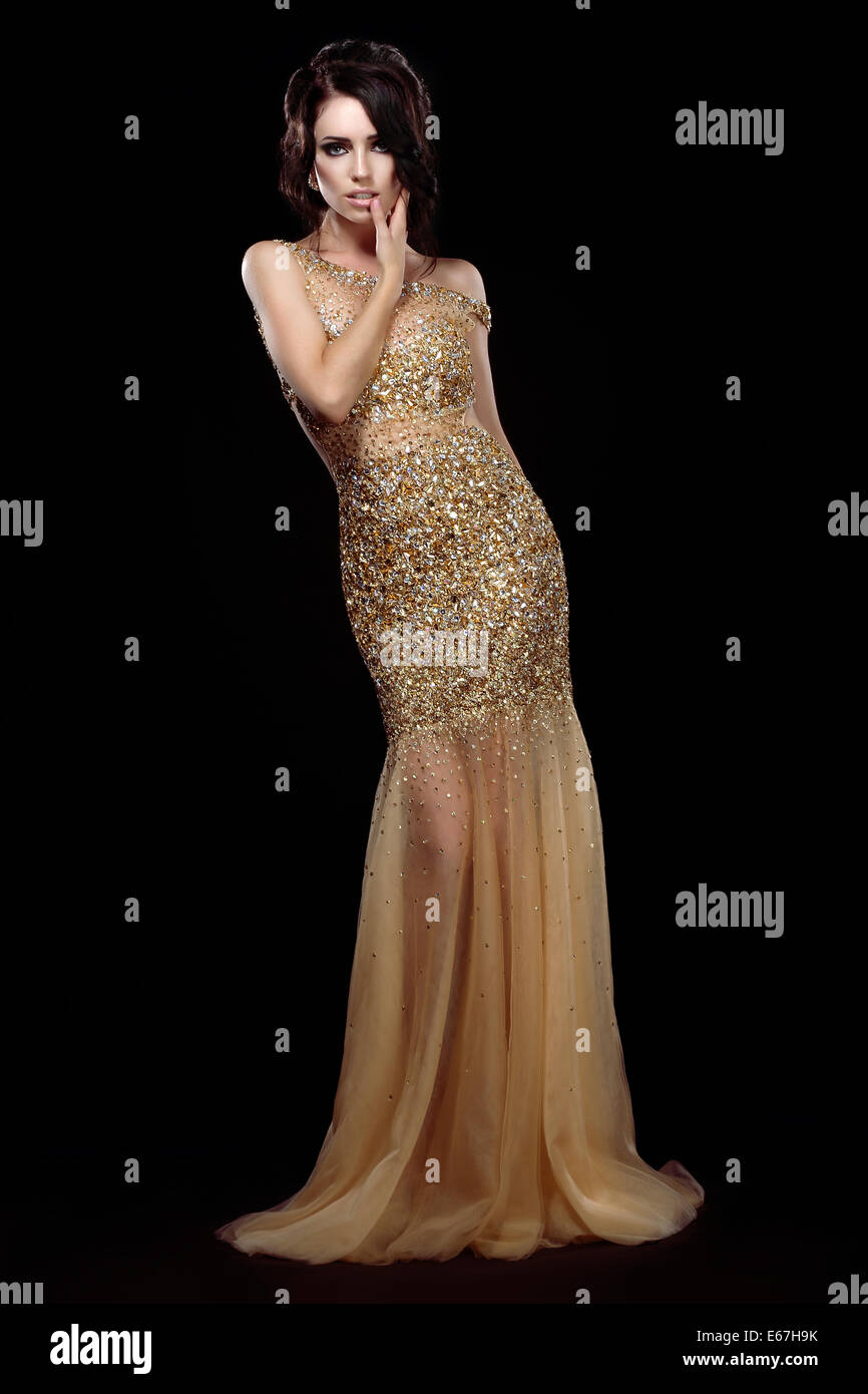 Elegance. Aristocratic Lady in Golden Long Dress over Black Background Stock Photo