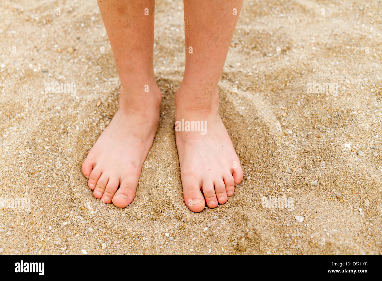 Bare feet of a young child in the sand - Stock Image