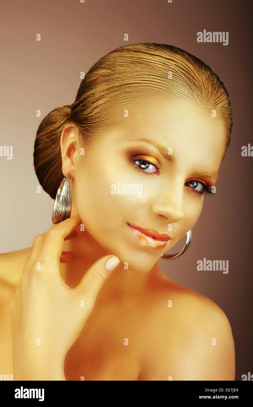 Fascinating Lady with Silver Earrings and Silky Golden Skin - Stock Image