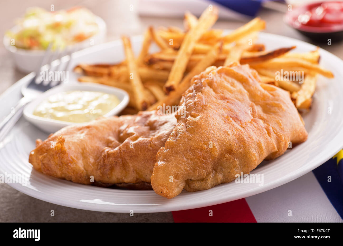 A plate of delicious fish and chips with tartar sauce and coleslaw. - Stock Image