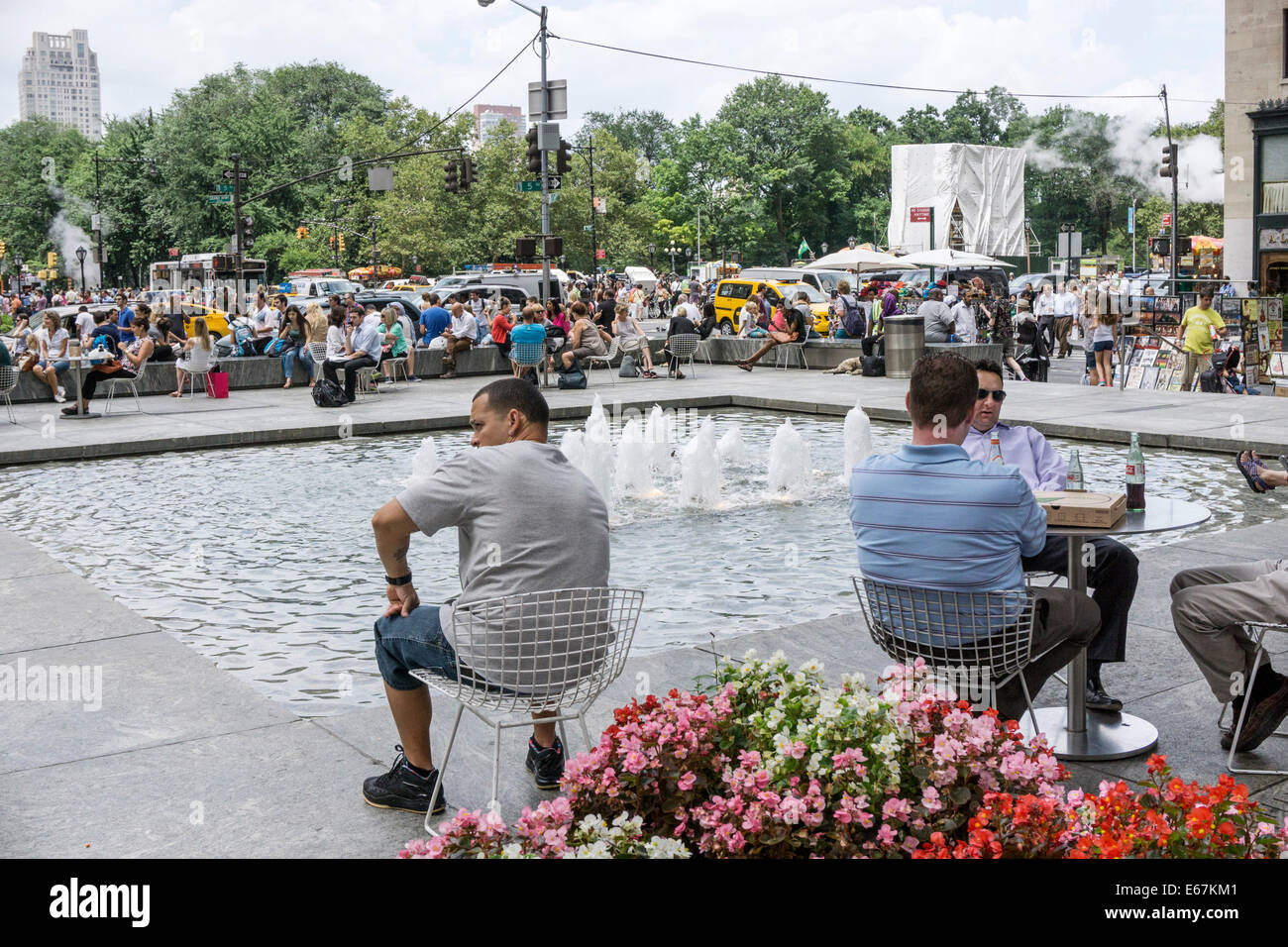 people sit relaxing next to pool & fountain at General Motors Plaza with view of crowds thronging Fifth Avenue sidewalks Stock Photo