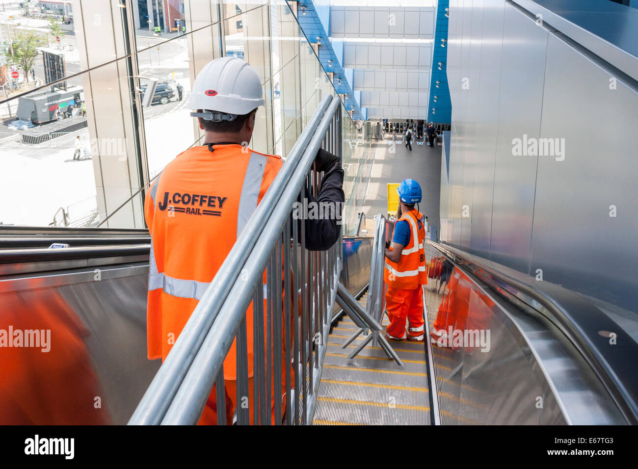 Workmen removing safety barriers down a public escalator after a