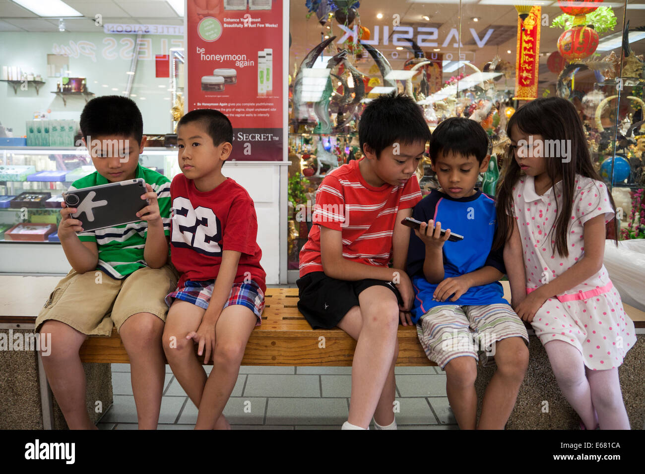 Asian children playing video game on their tablets in the Asian Garden Mall, Westminster, Orange County, California, - Stock Image