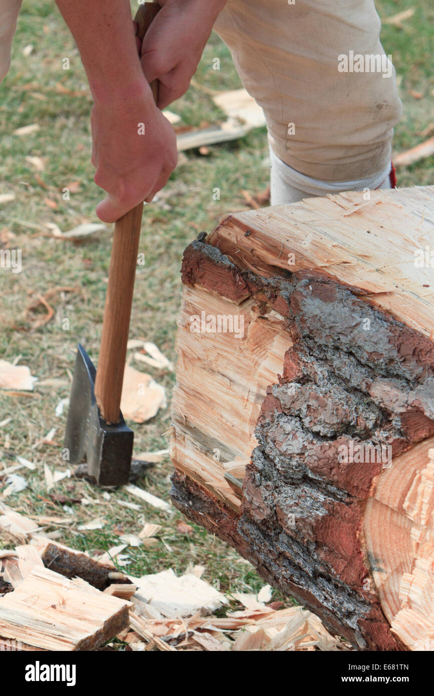 Man squaring a log with an ax for use in manual construction later. - Stock Image