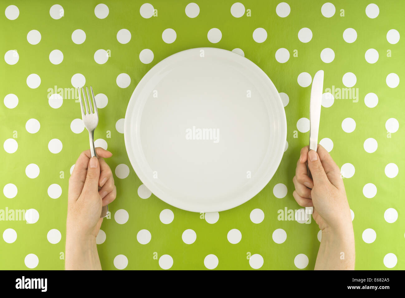 Female hands at dinner table holding fork and a knife above empty flat white plate, dieting concept. - Stock Image