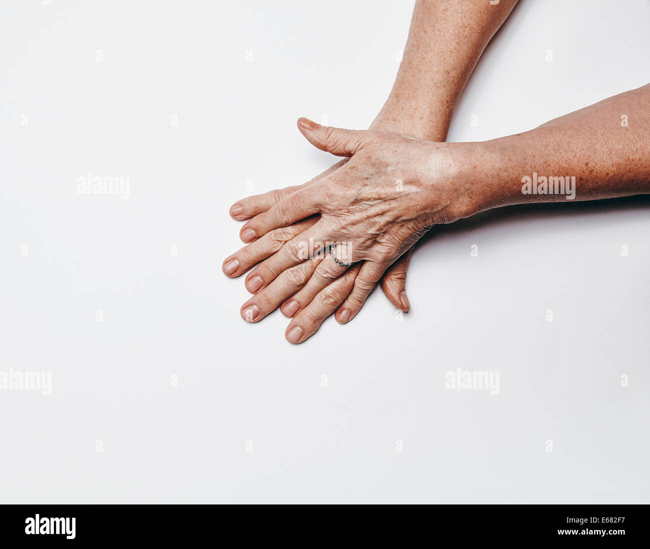 Top view of old female hands with fingers crossing. Senior woman hands isolated on white background  with copy space. - Stock Image