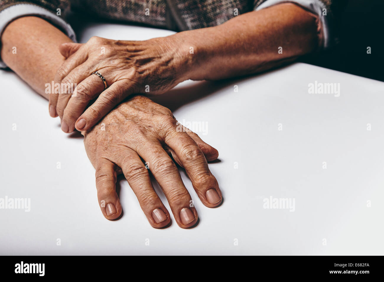 Close-up image of senior woman sitting by a table with focus on her hands. Old female hands on a desk. - Stock Image