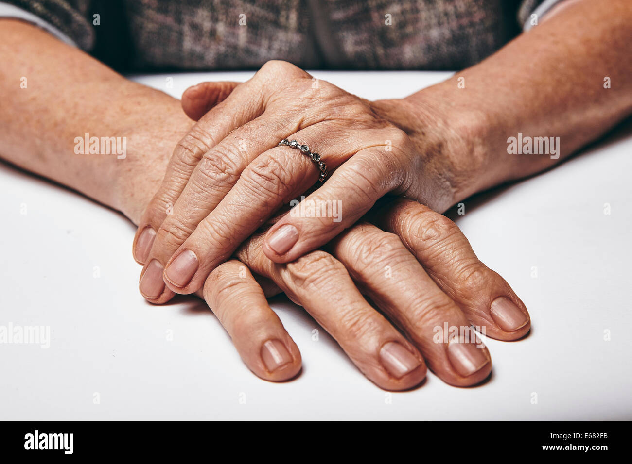 Macro of an old lady sitting with her hands clasped on a table. Elderly woman's hands with a ring resting on - Stock Image