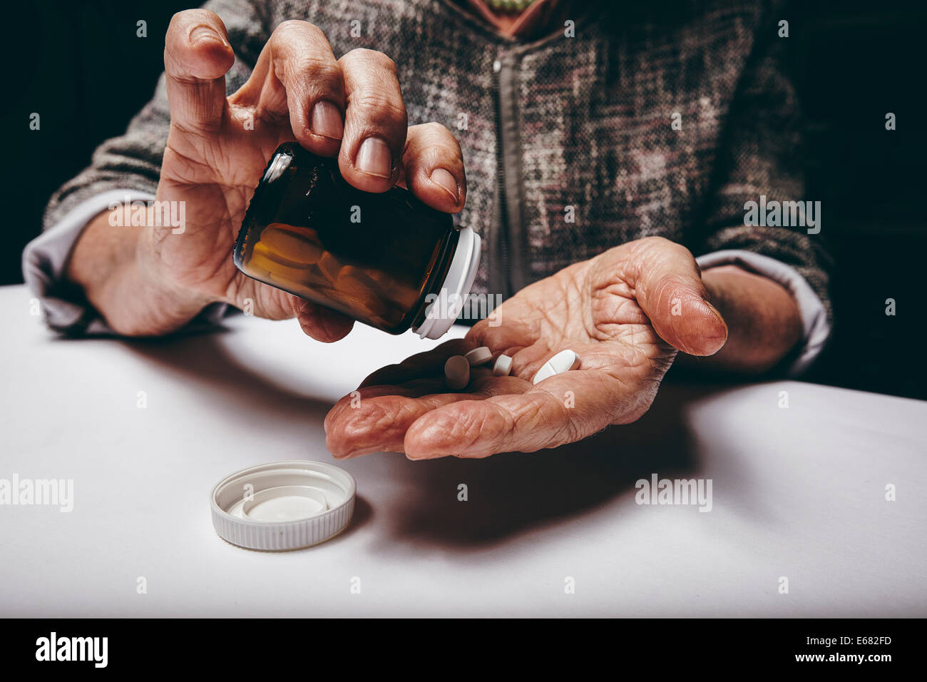 Cropped view of elderly woman taking prescription medicine from pill bottle. Senior female's hands pouring pills - Stock Image