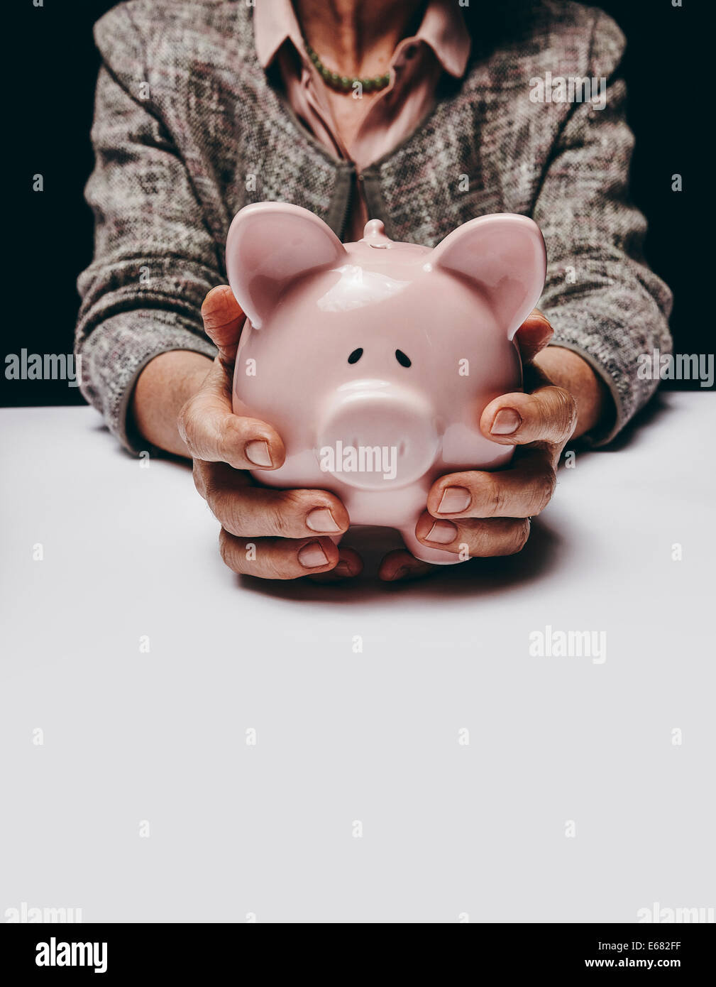 Cropped studio shot of senior female hands holding a coin bank while sitting at a table. Old woman holding a piggybank. - Stock Image